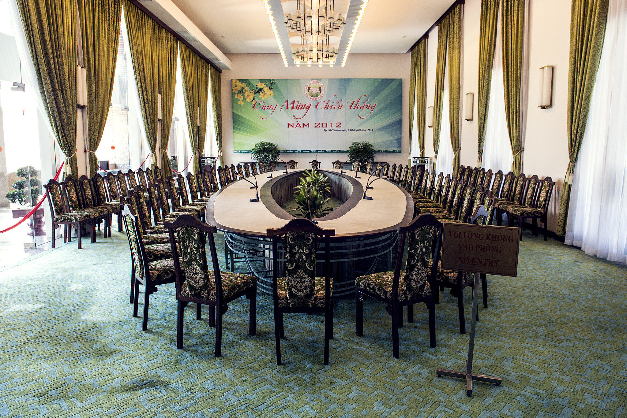 Grand conference room with oval table and brown ornate wooden chairs